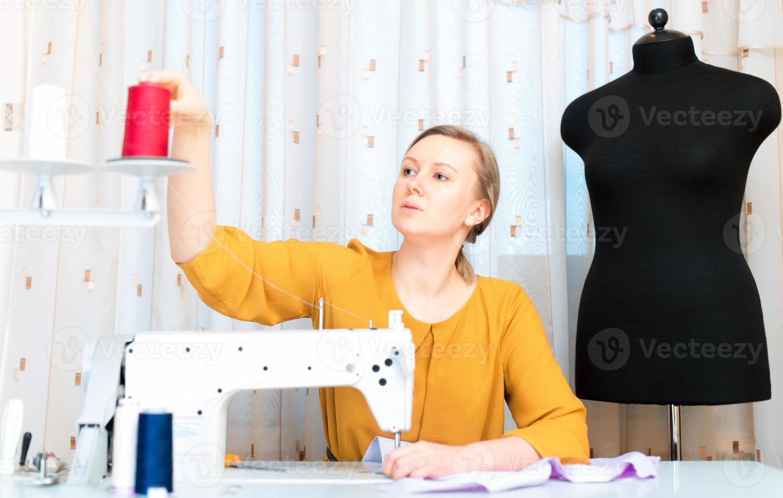 mulher que trabalha na máquina de costura na fábrica. foto