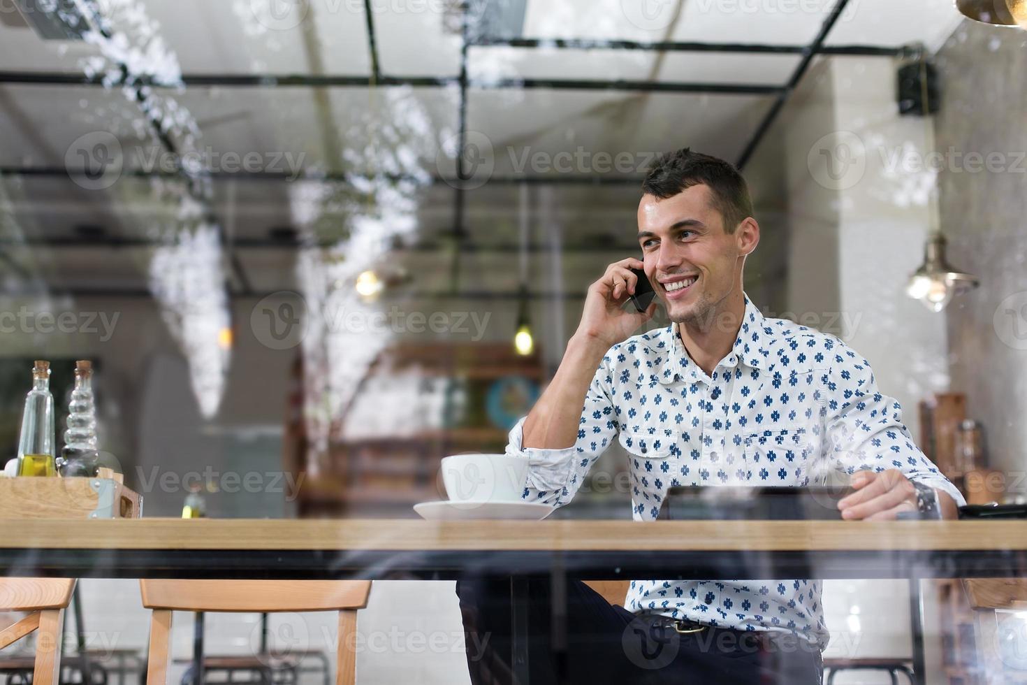 empresário em um café falando ao telefone foto