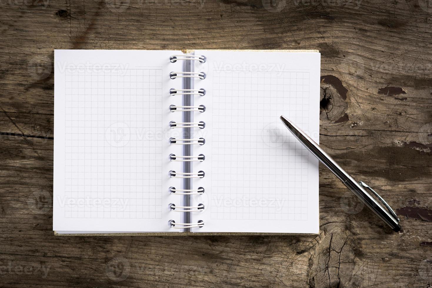caderno e caneta em fundo madeira foto