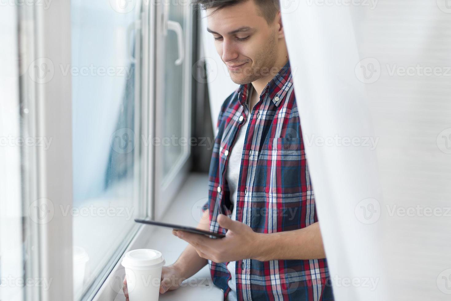 bonitão sorridente homem camisa xadrez perto da janela com foto