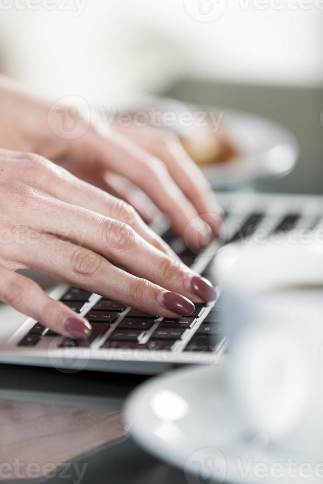 mãos de mulher, digitando em um teclado foto