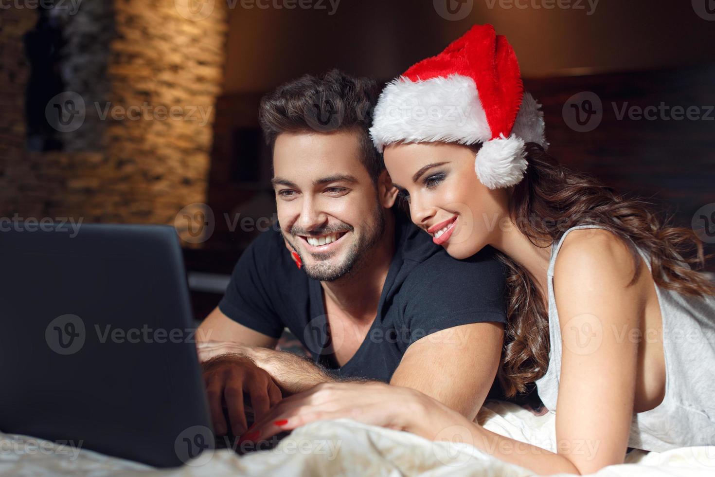 jovem casal procurando presentes de natal on-line foto