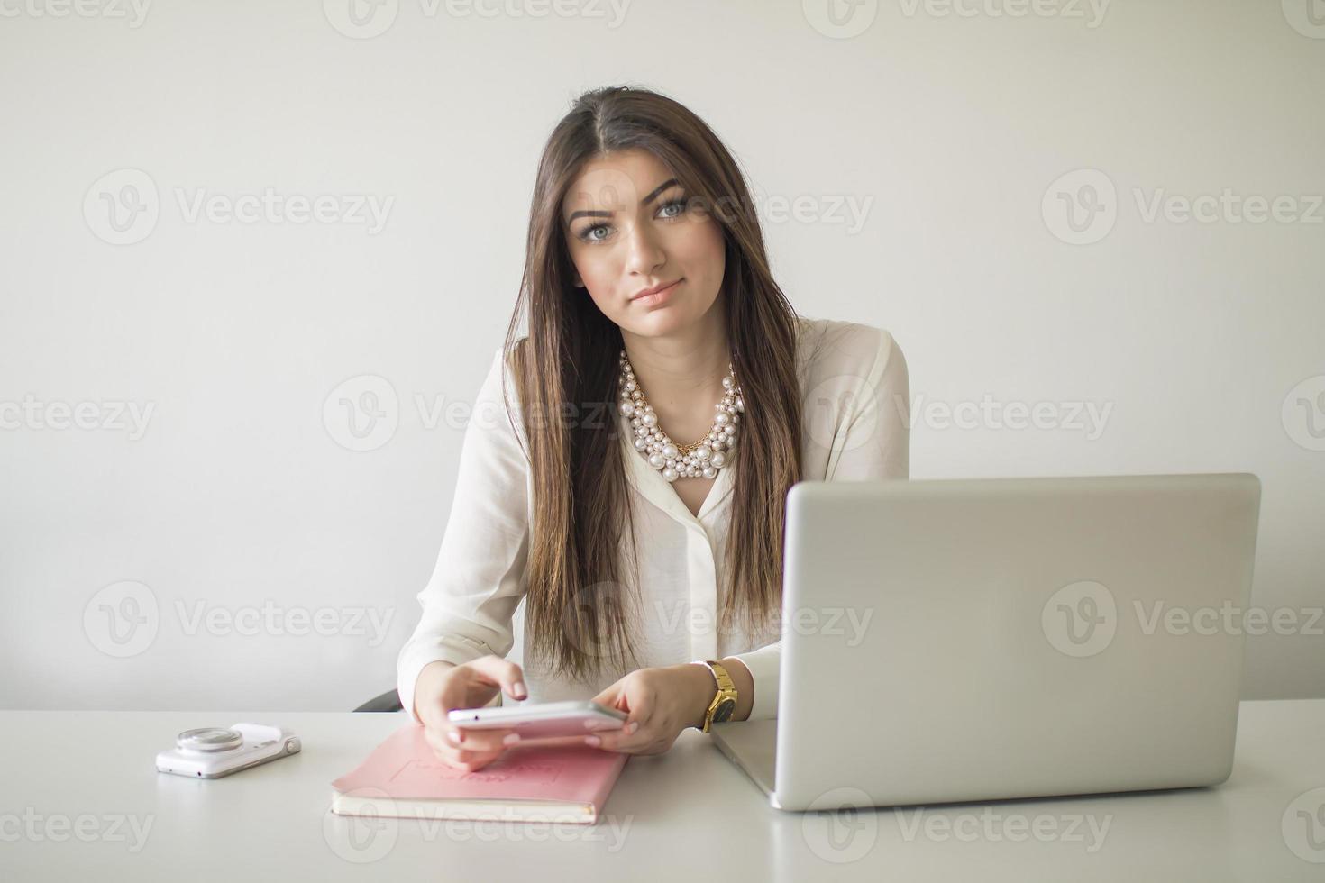 mulher jovem e bonita feliz usando laptop, dentro de casa foto