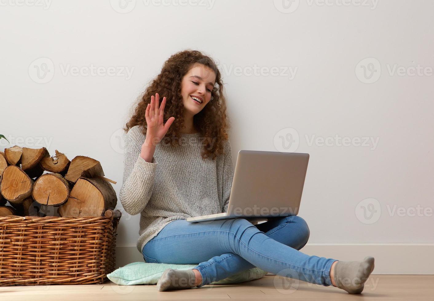 adolescente usando laptop e acenando Olá no chat foto