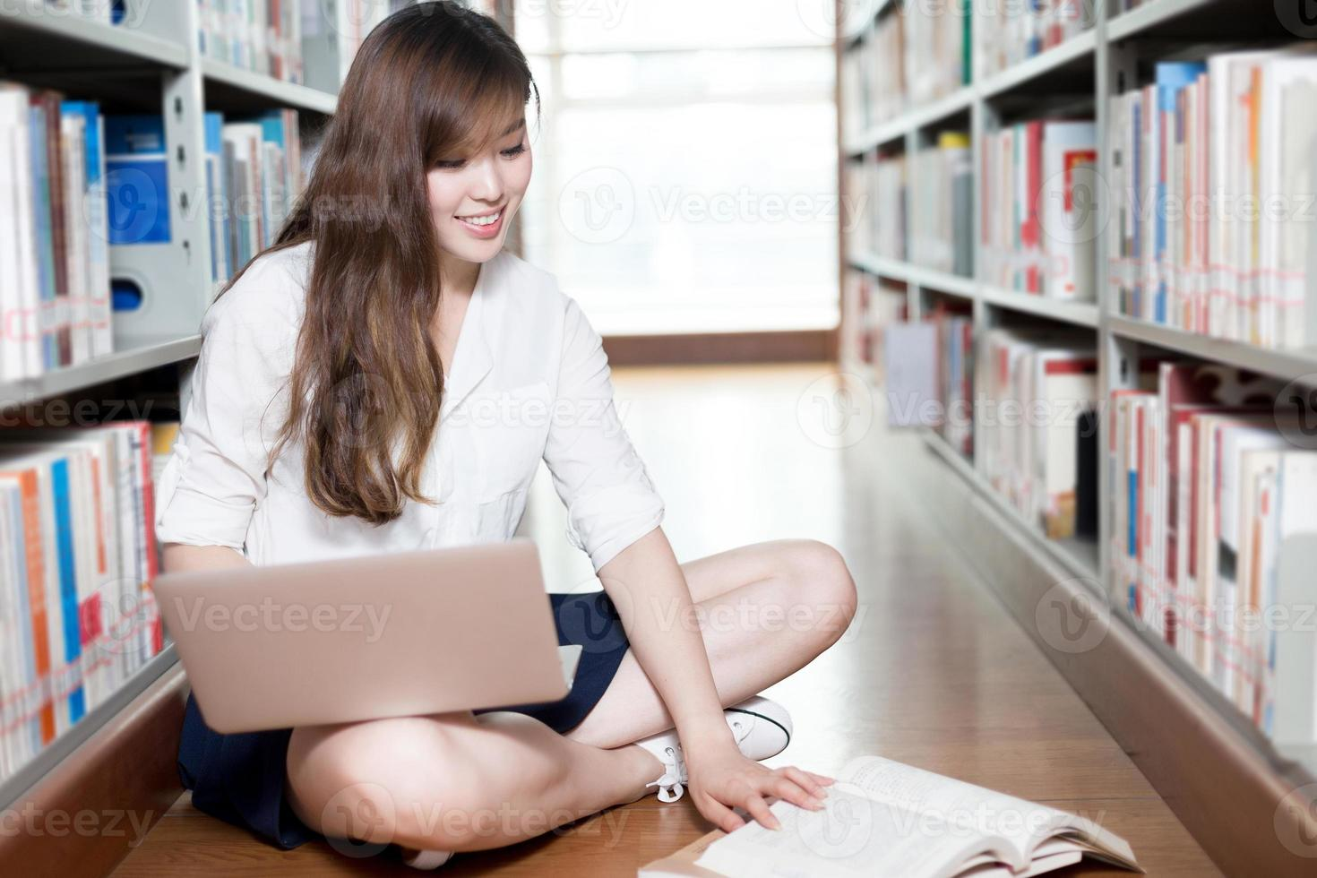 bela aluna asiática estudando na biblioteca com o laptop foto