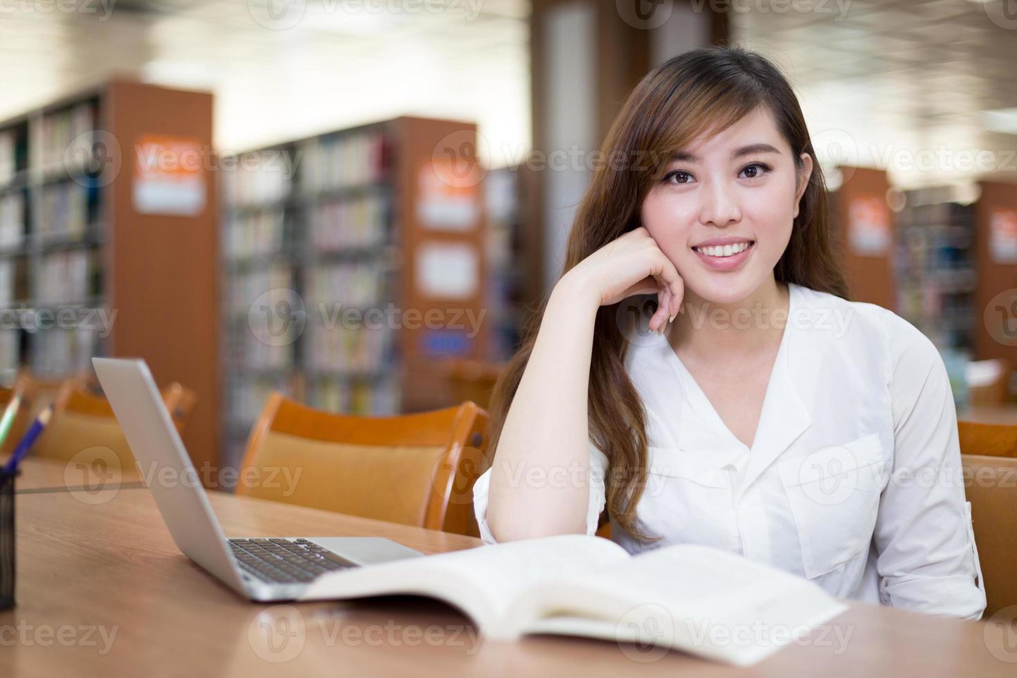 bela aluna asiática usando laptop para estudo na biblioteca foto
