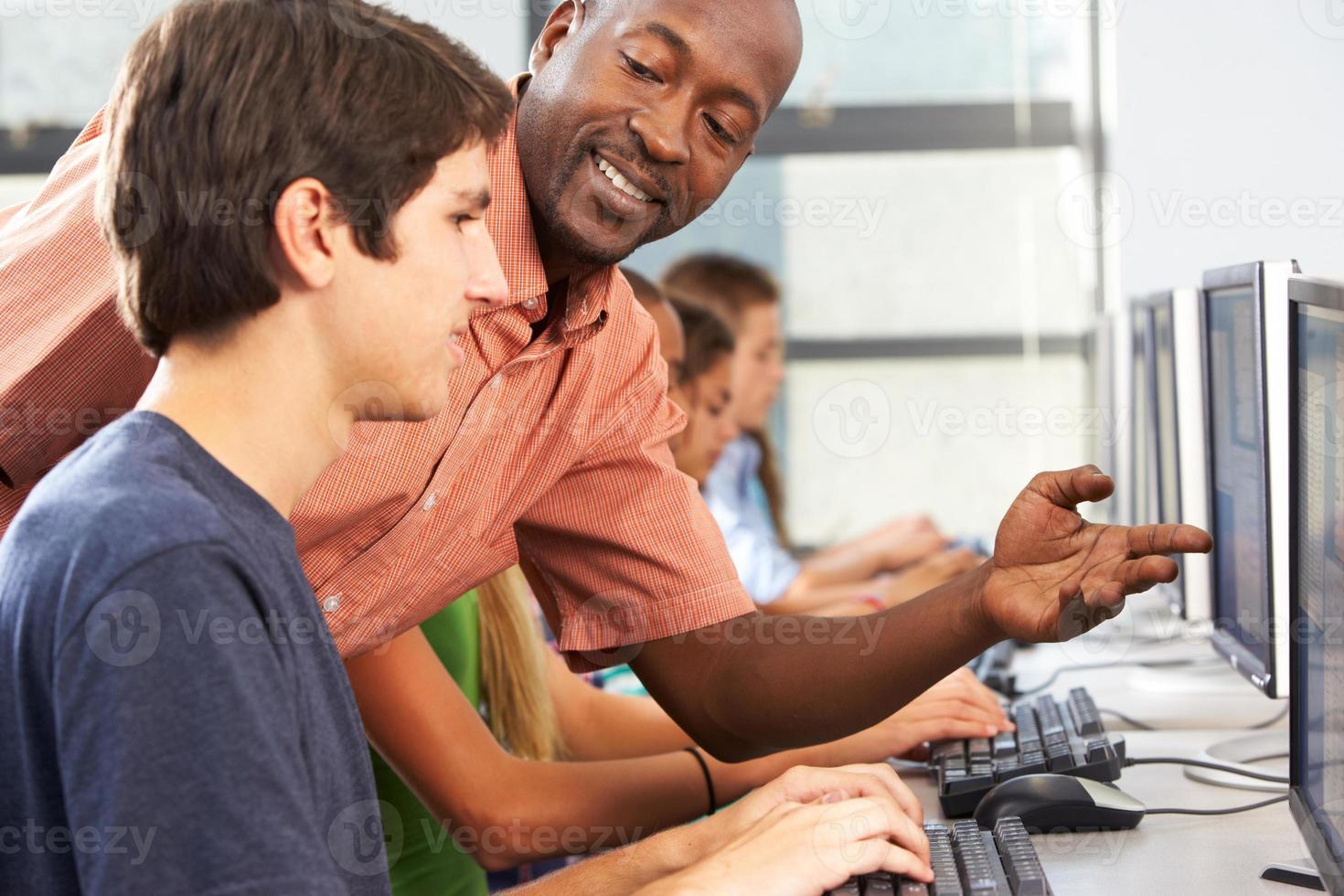 professor e alunos sentados em computadores foto