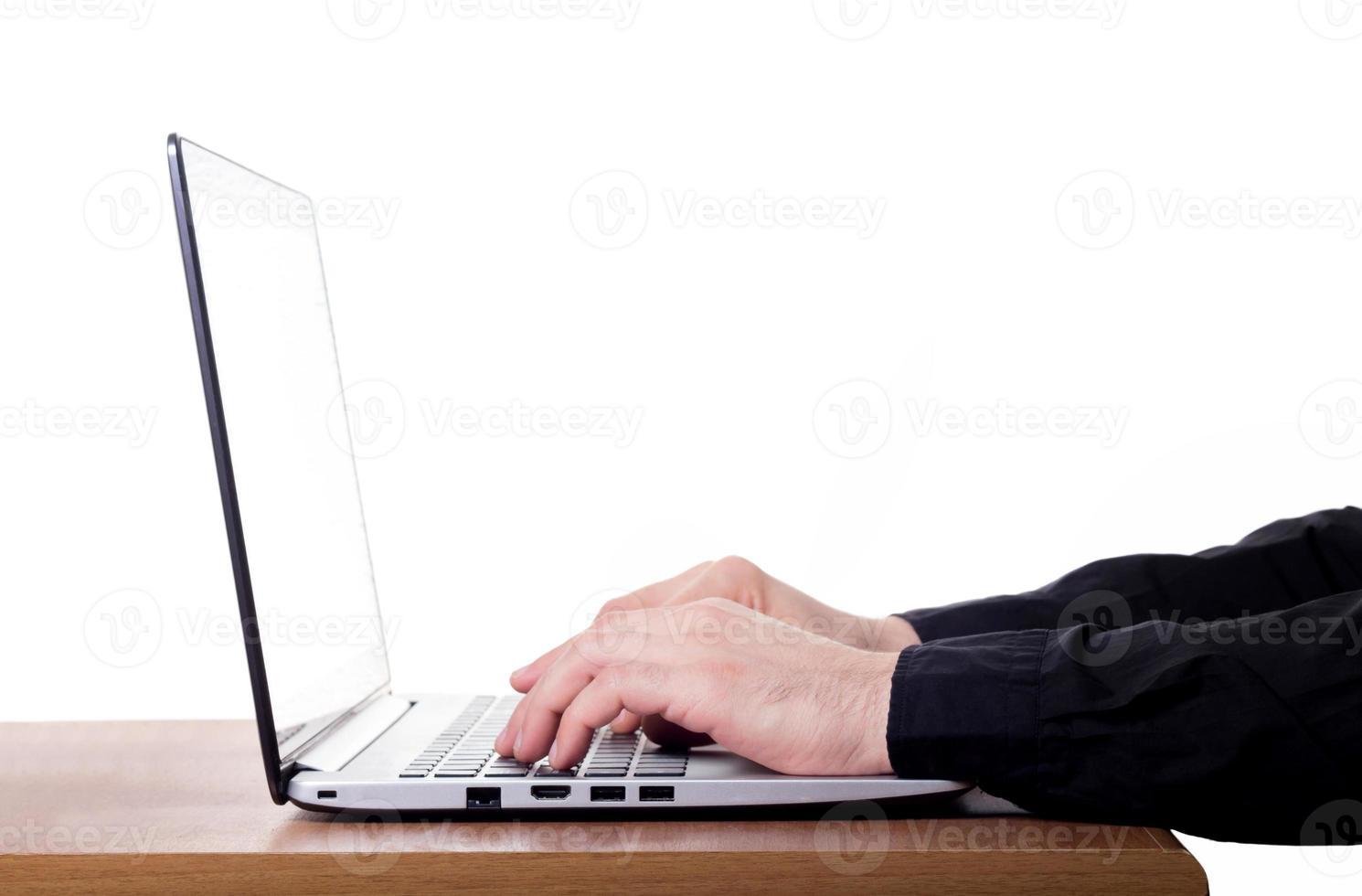dedos do homem no teclado do laptop foto
