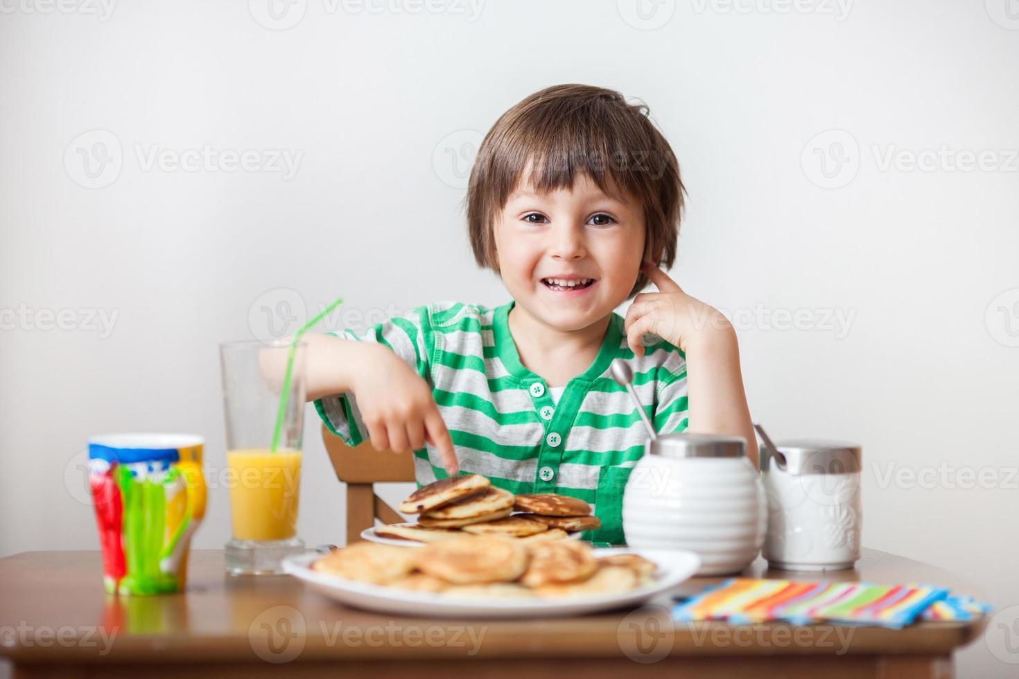 menino caucasiano doce, comendo panquecas foto