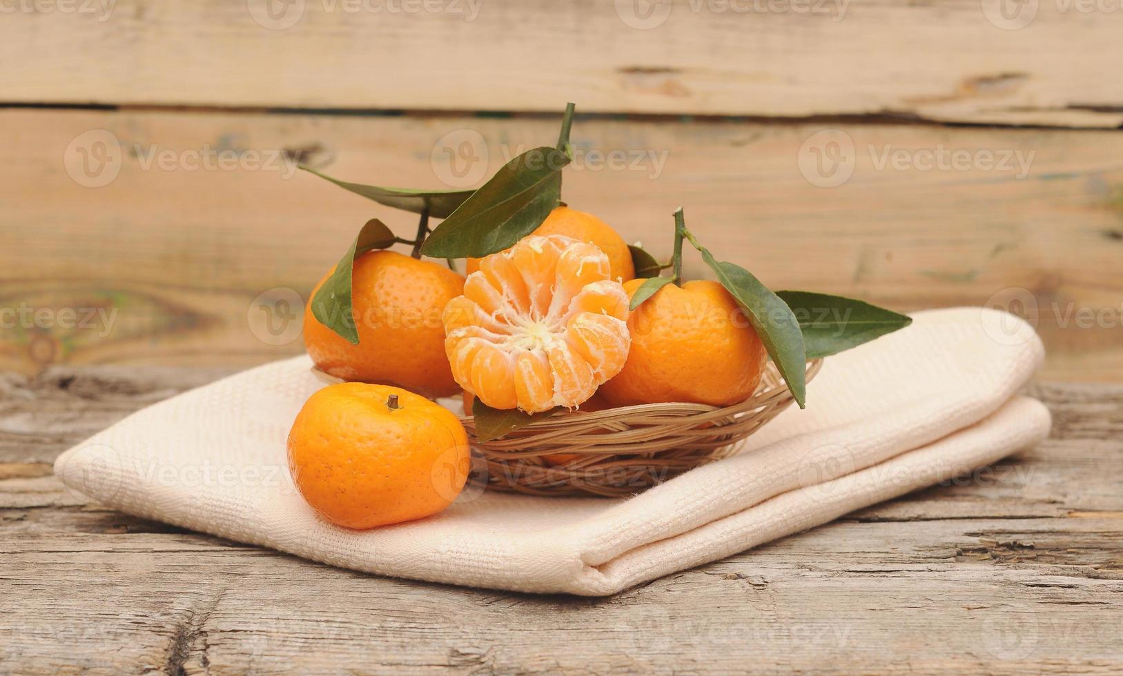 tangerinas com folhas em uma cesta bonita, na mesa de madeira foto