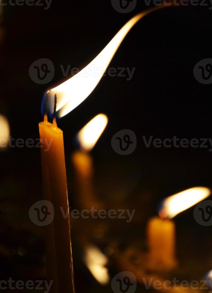 queimando velas em uma igreja em um fundo escuro foto