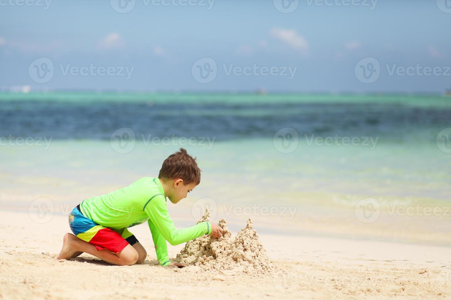 menino caucasiano, construindo o castelo de areia na praia tropical foto