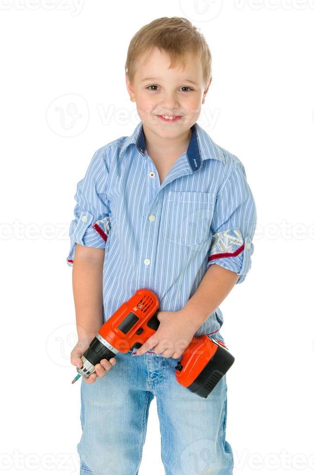 menino bonito caucasiano está segurando uma chave de fenda foto