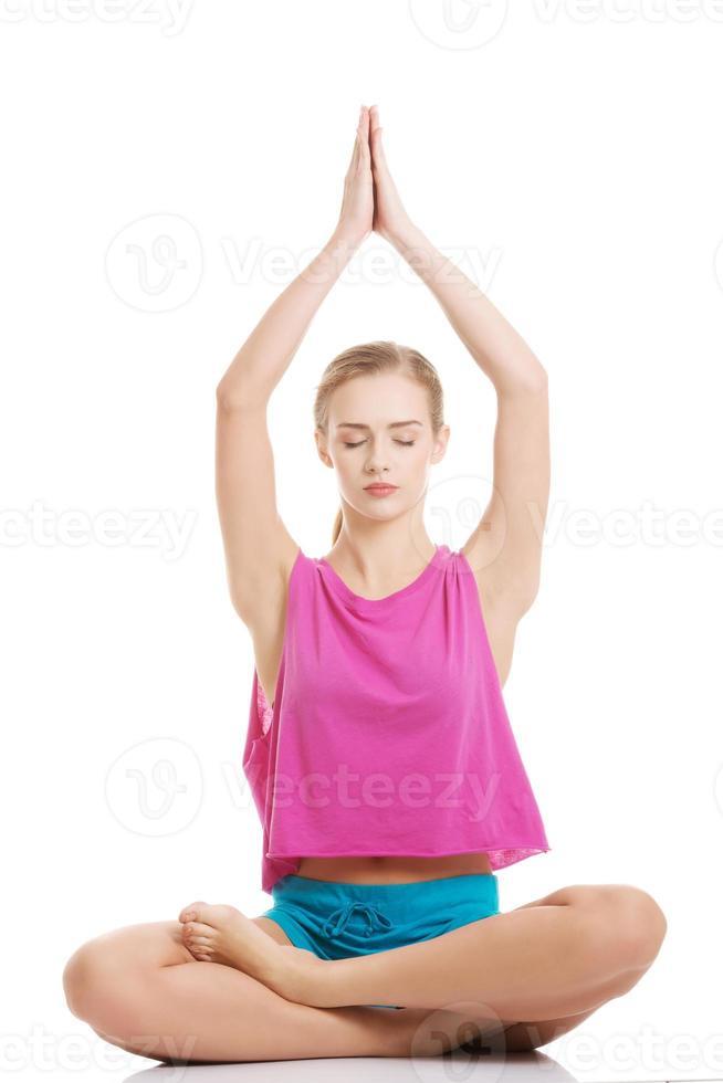bela jovem caucasiana está exercitando, fazendo yoga. foto