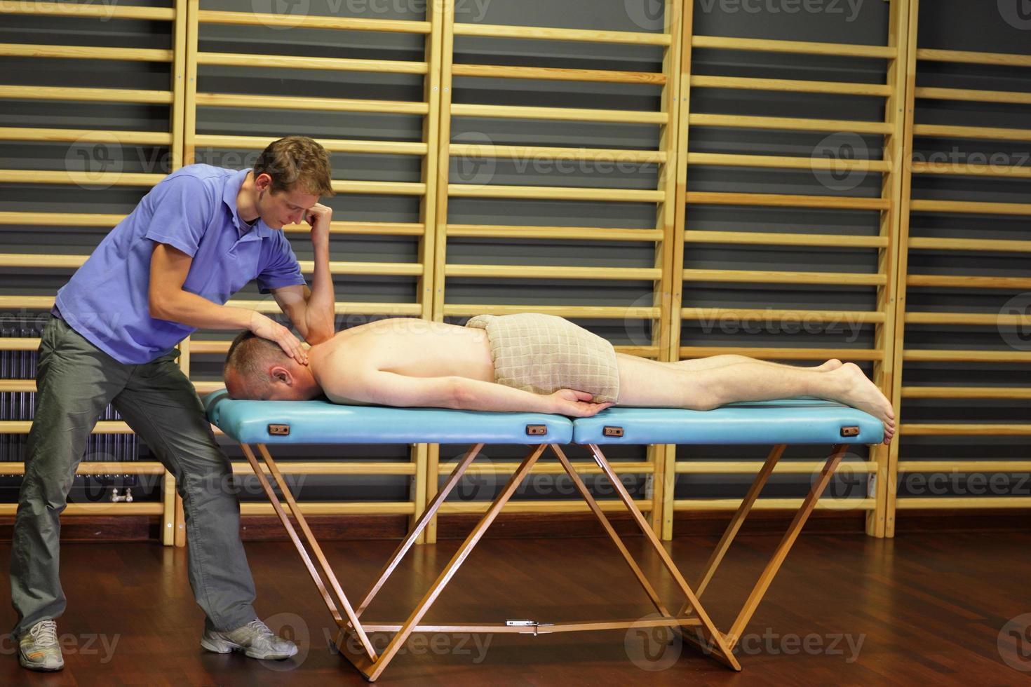 terapeuta masculino massageando meia idade homem caucasiano pescoço foto