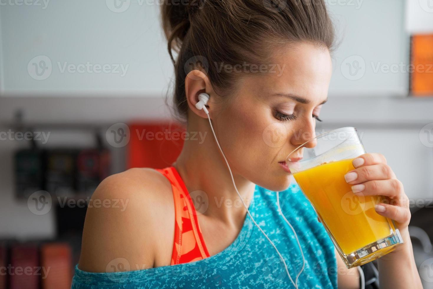 retrato de mulher de aptidão bebendo batido de abóbora na cozinha foto