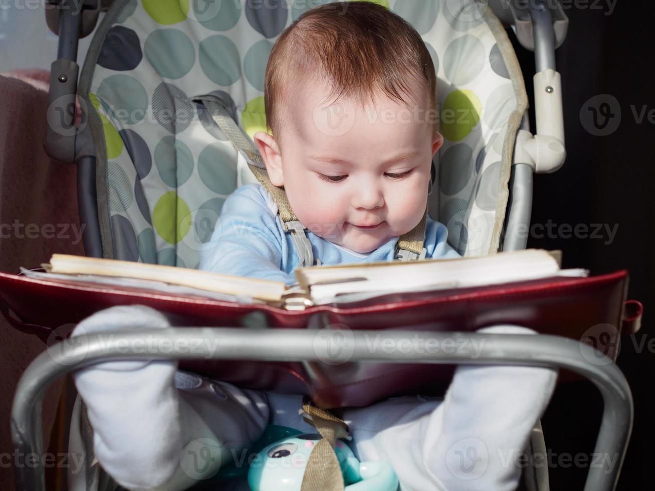 pequeno menino caucasiano sentado em chear com o bloco de notas foto