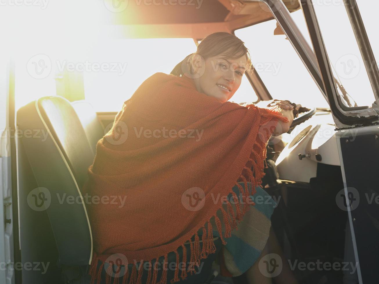 mulher feliz no banco do motorista da van foto