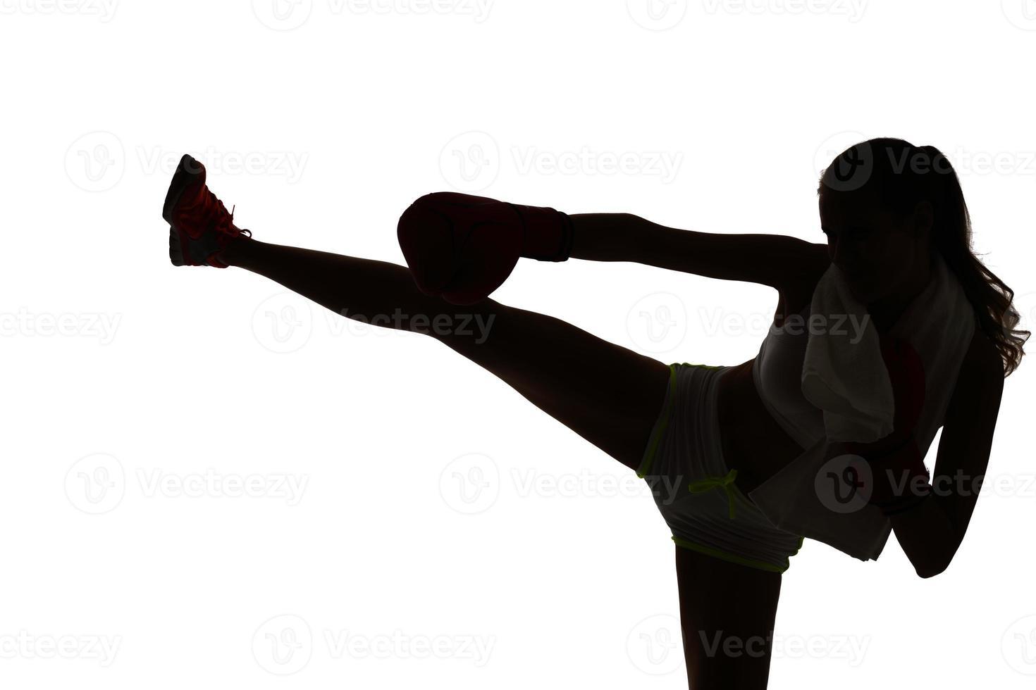 uma mulher caucasiana, boxe, exercitando-se no estúdio de silhueta isola foto