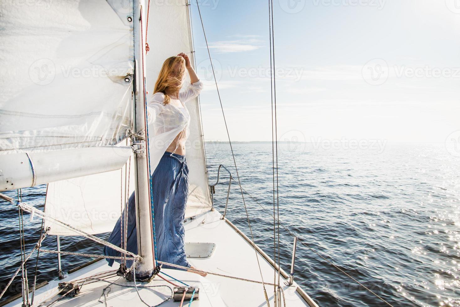 jovem mulher caucasiana em um veleiro olhando para o horizonte foto