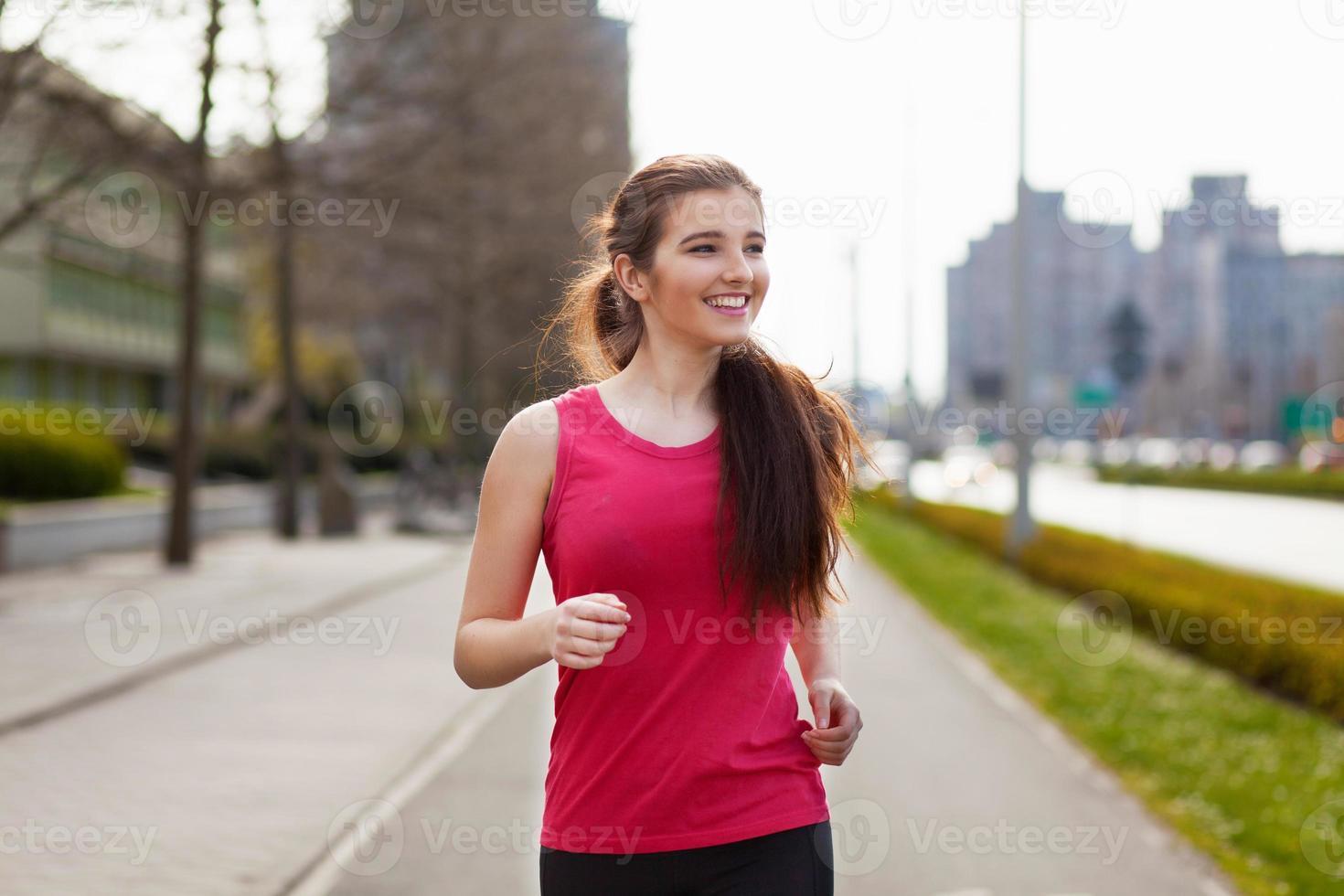 jovem mulher bonita correndo na cidade foto