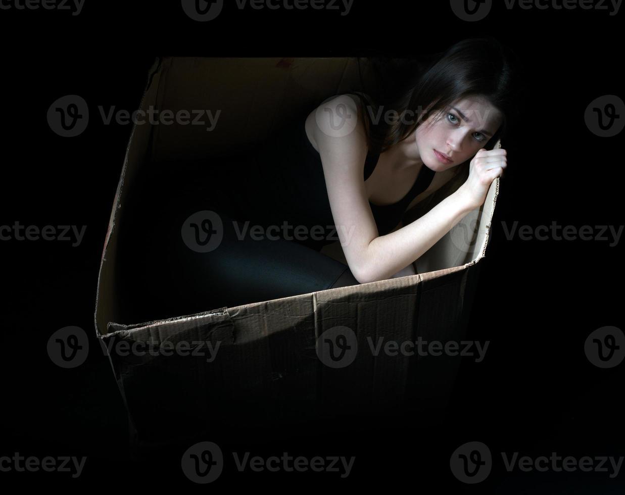 conceito de sem-teto. menina chateada em caixa de papelão foto