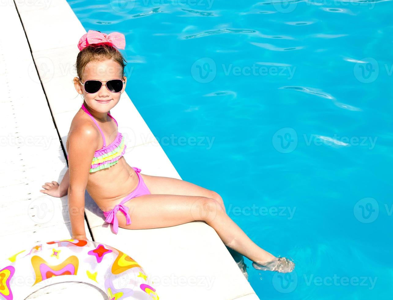 menina sorridente, sentado perto da piscina foto