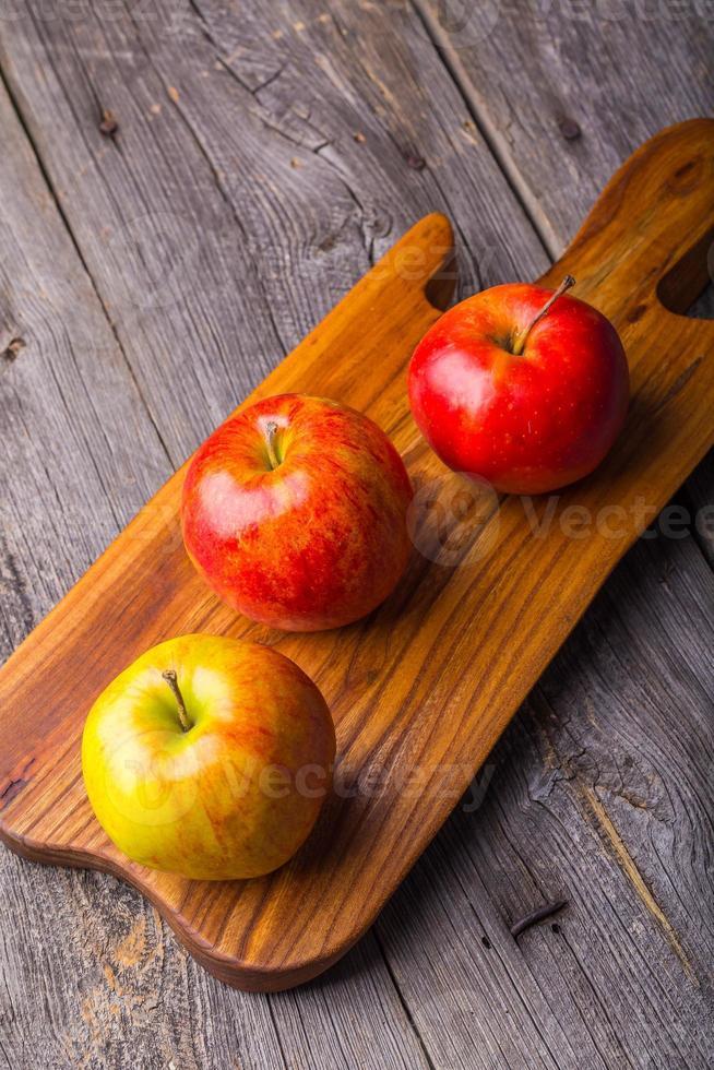 maçãs frescas na tábua de madeira foto