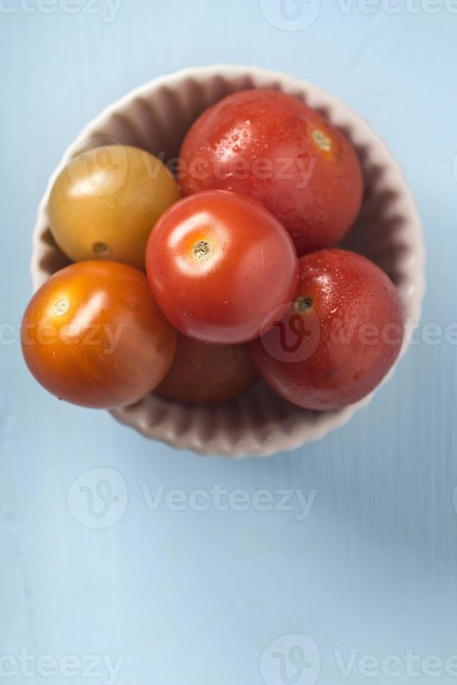 tomate cereja em uma tigela sobre fundo azul de madeira foto