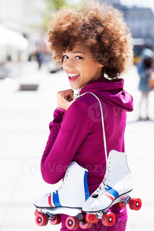mulher afro-americana segurando patins foto