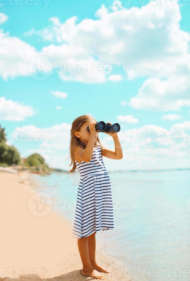 criança olhando através de binóculos na extensão do mar foto