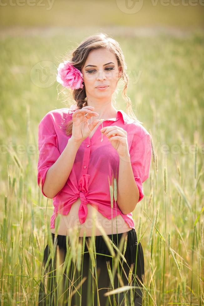 jovem de rosa no campo de trigo dourado foto