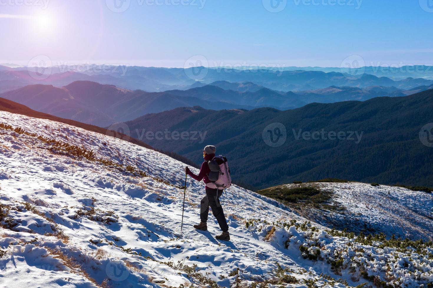 um caminhante caminhando na neve gelo terreno ampla vista para a montanha foto
