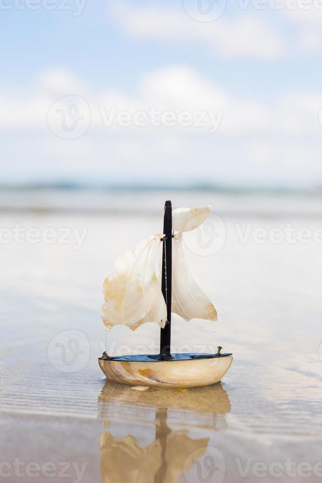barco a vela de brinquedo na praia foto