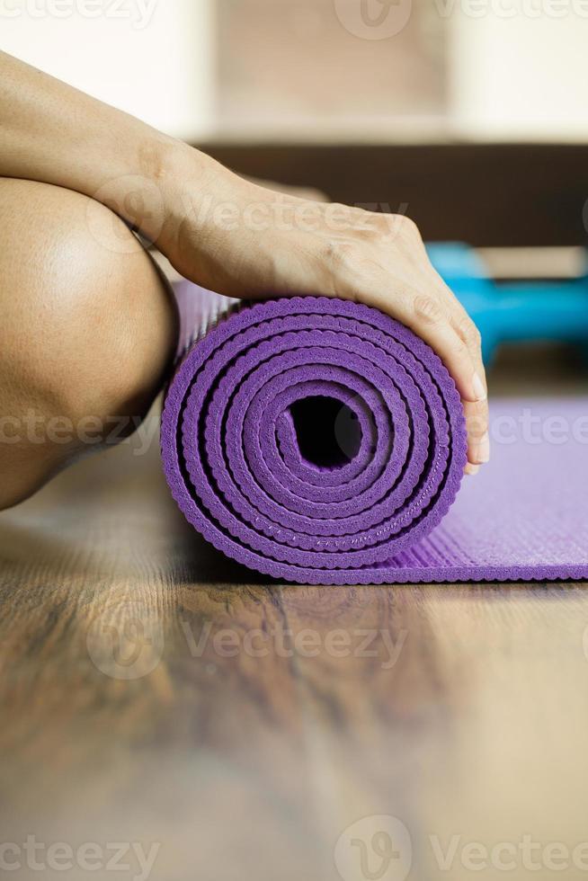 mulher segurando um tapete de ioga no clube de esporte foto