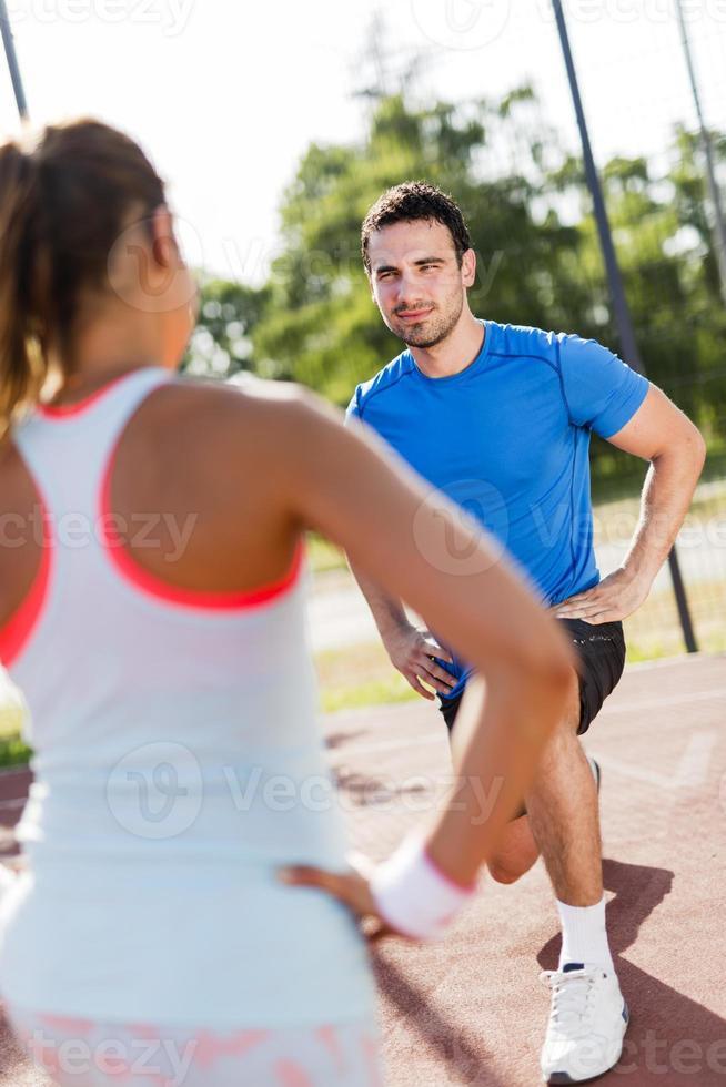 jovem atlético homem e mulher, estendendo-se ao ar livre foto