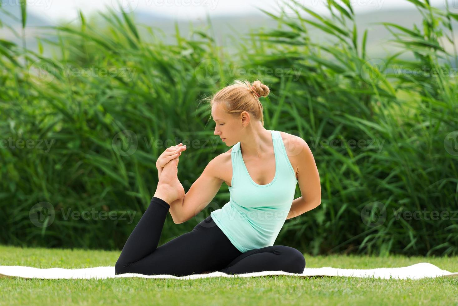 mulher fazendo yoga pose de pombo rei de pernas foto