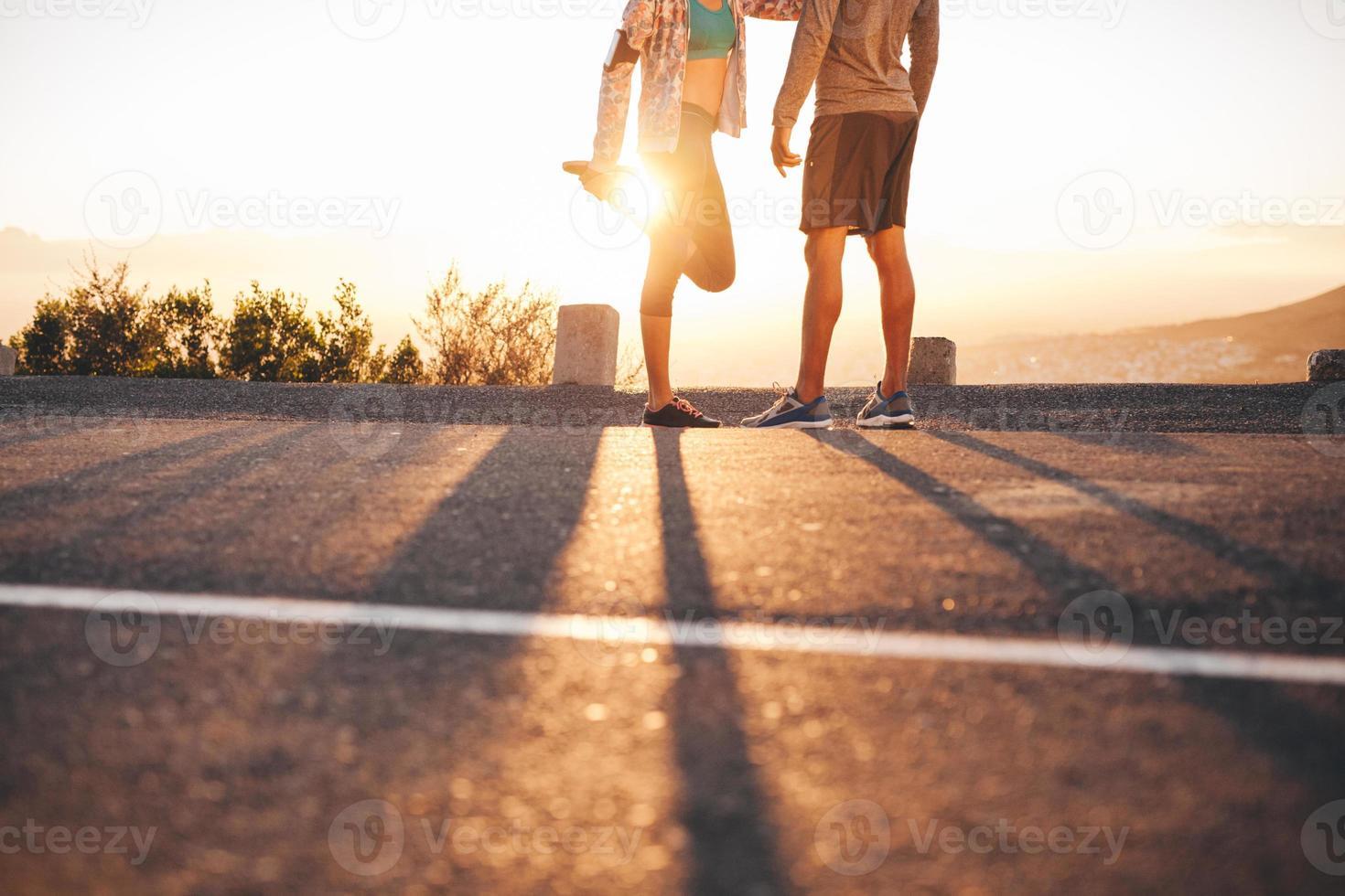 ajuste jovem casal se aquecendo antes de uma corrida foto
