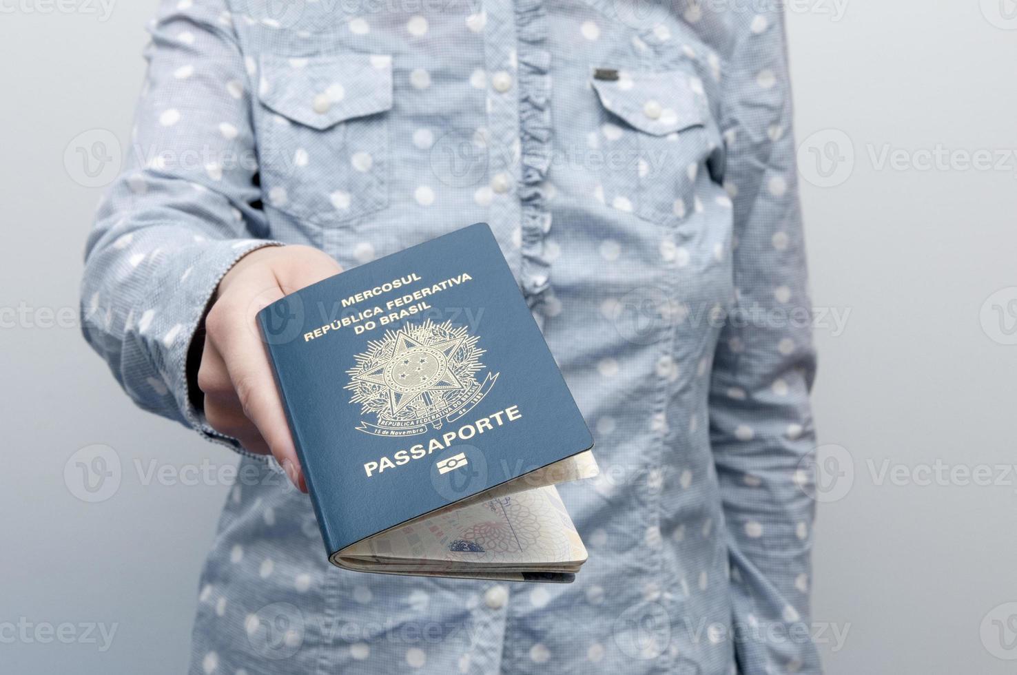 mulher caucasiana, segurando um passaporte brasileiro foto
