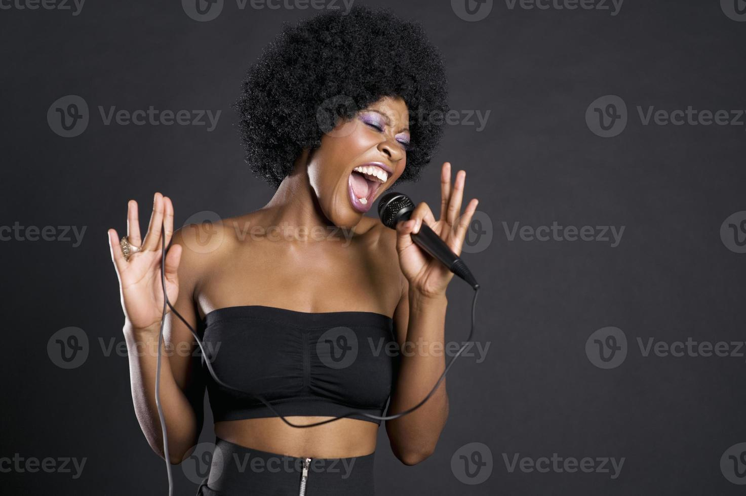 mulher afro-americana cantando no microfone foto