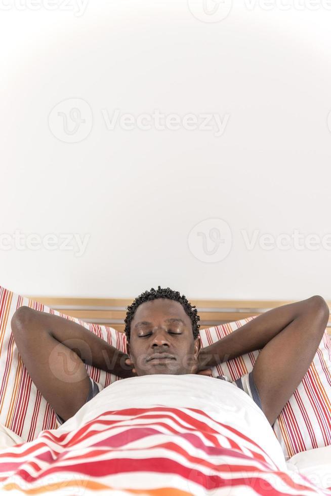 homem afro-americano pacífico, dormindo na cama foto