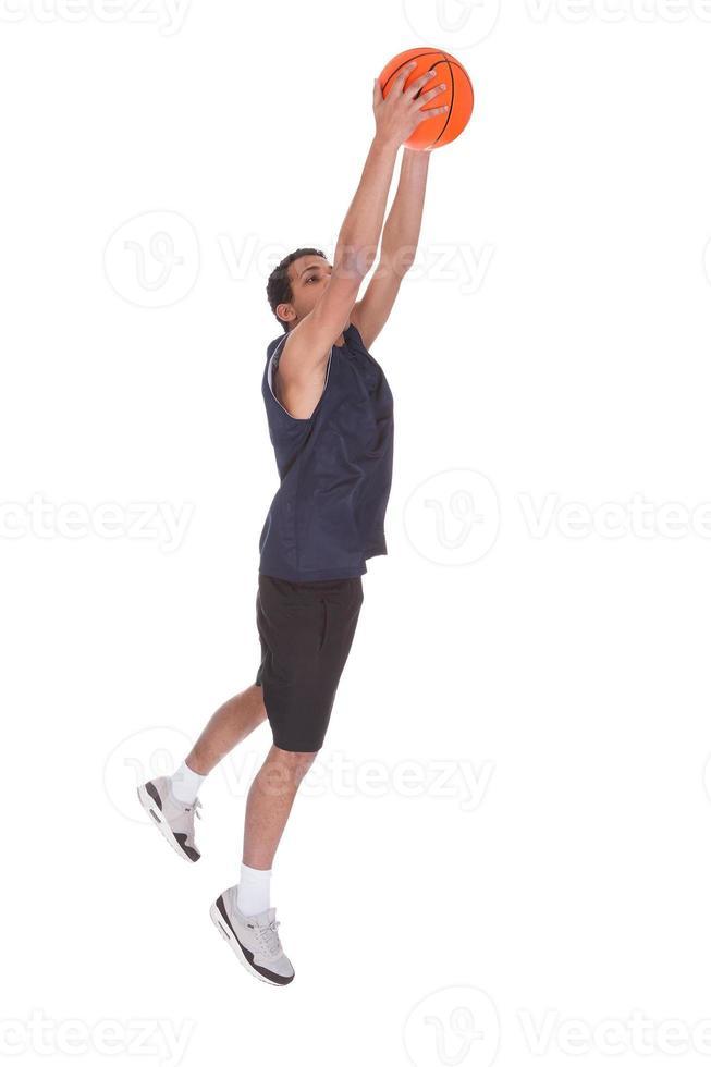 desportista de basquete fazendo slam dank foto