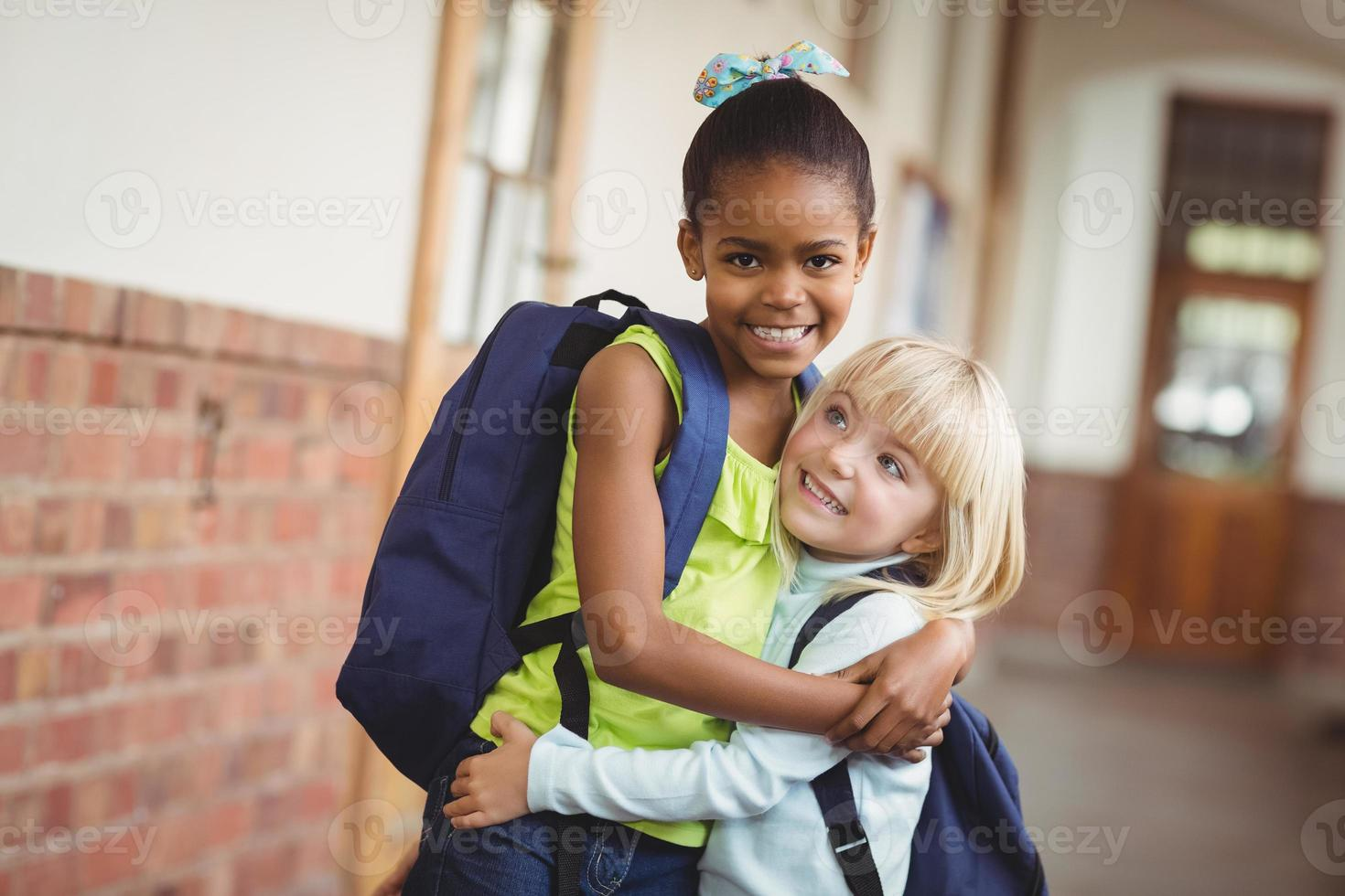 alunos bonitos abraçando no corredor foto
