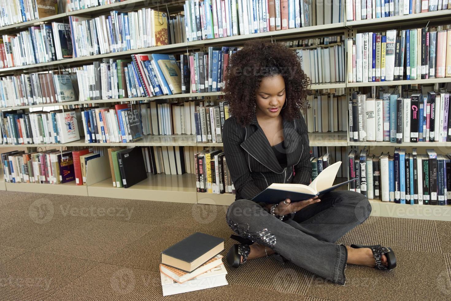 jovem mulher na biblioteca foto
