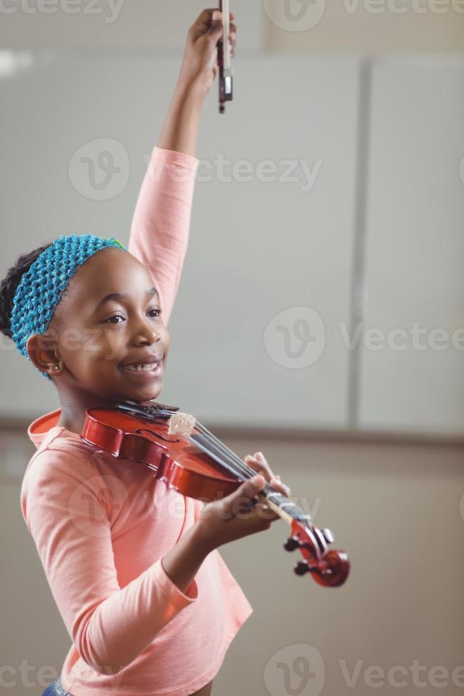 aluno sorridente tocando violino na sala de aula foto
