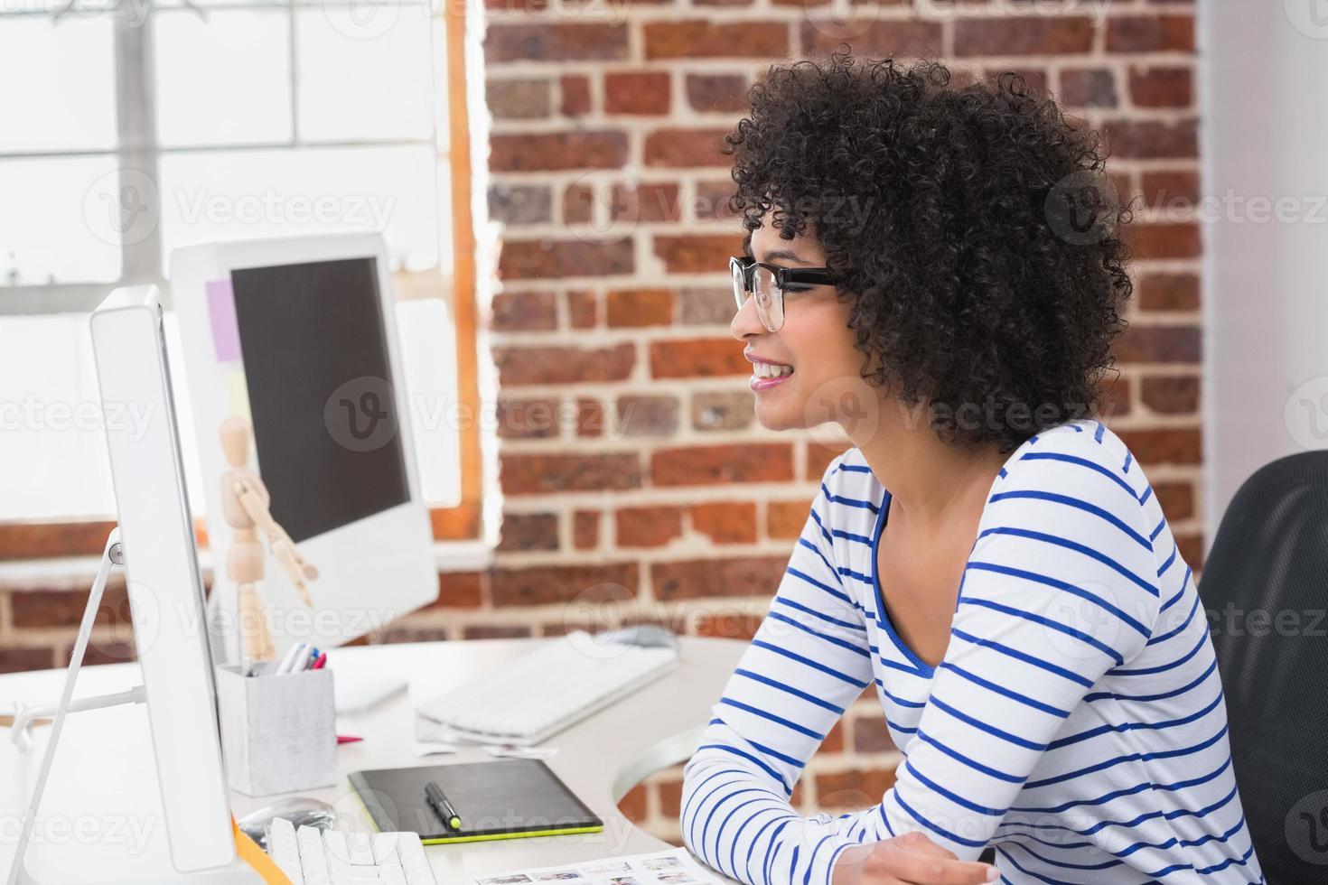 editor de fotos sorridente usando o computador no escritório