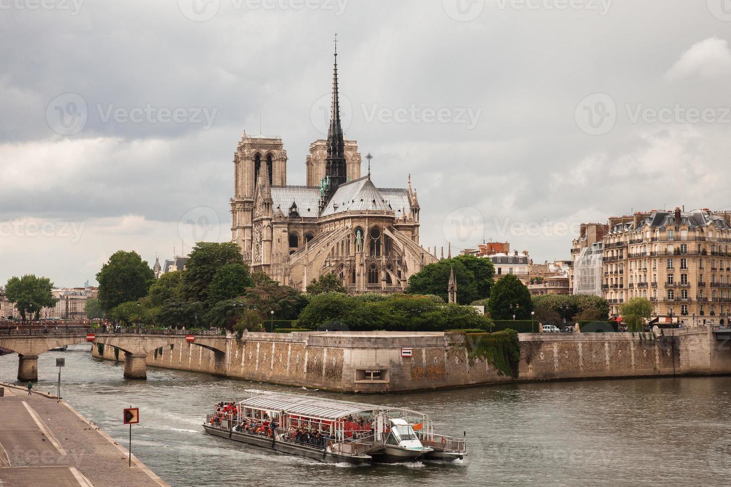 Notre Dame com barco turístico no Sena em Paris foto