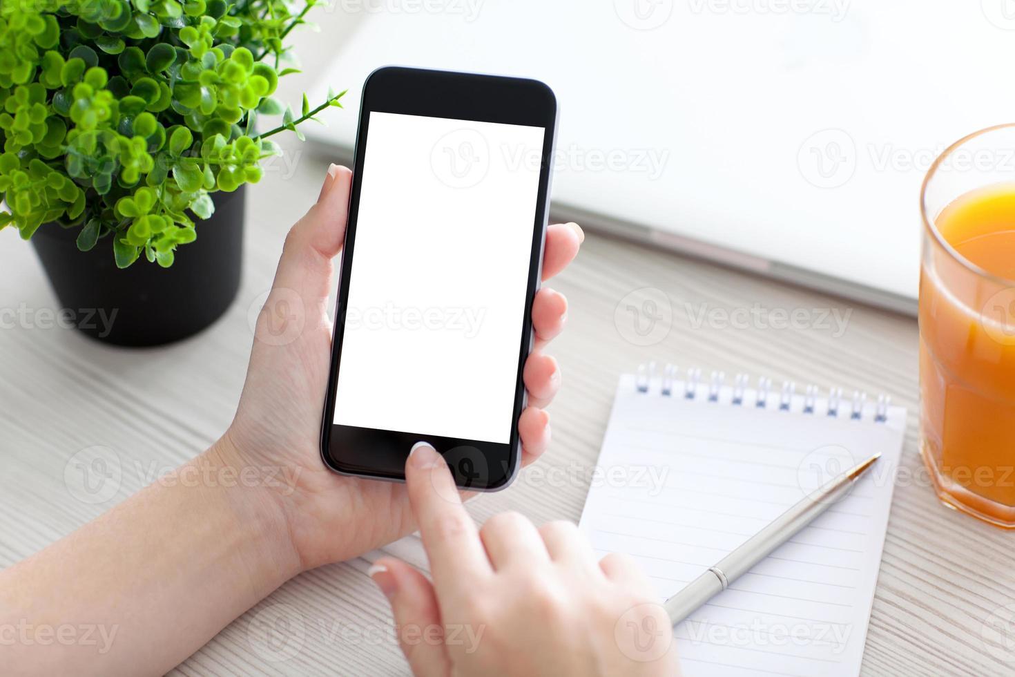 mão de mulheres segurando o telefone com tela isolada em cima da mesa foto