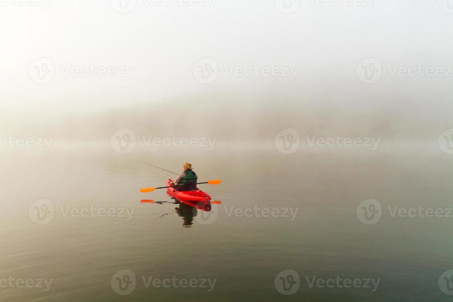 pescador no caiaque vermelho, névoa da manhã foto