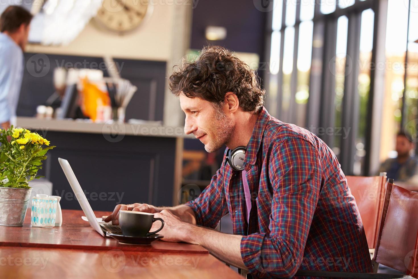 homem trabalhando no computador na cafeteria foto
